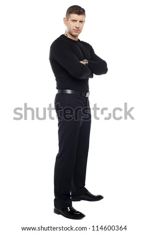 Handsome young bodyguard, full length portrait. Arms folded - stock photo