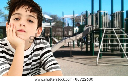 Handsome young boy child bored and waiting at park playground. - stock photo