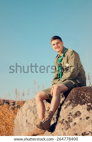 Handsome Young Boy Scout Sitting on the Big Rock at the Field on a Sunny Day While Smiling at the Camera. - stock photo