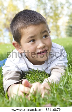 Handsome young boy with bright smile missing one front tooth laying in the grass