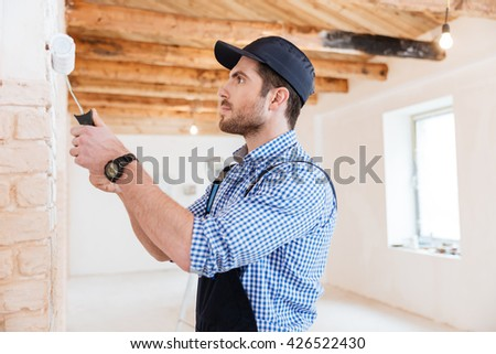 Handsome young builder working with a paint roller indoors - stock photo