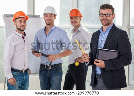 Handsome young builders and architect are working on a new project. They are discussing the plan of building and drawing sketches. The architect is holding a laptop. They are smiling - stock photo
