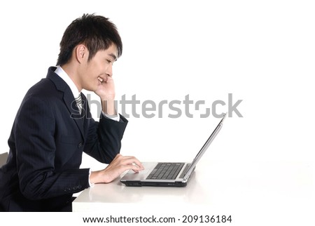 handsome young business asian man using cell phone and working on laptop