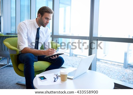 Handsome young business entrepreneur sitting in an open modern office space, looking at his laptop and making notes in his diary - stock photo