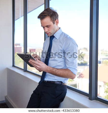 Handsome young business entrepreneur standing in a new office with large windows, typing on the screen of his digital tablet - stock photo