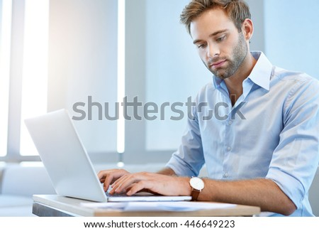 Handsome young business executive using his laptop computer to work through some paperwork