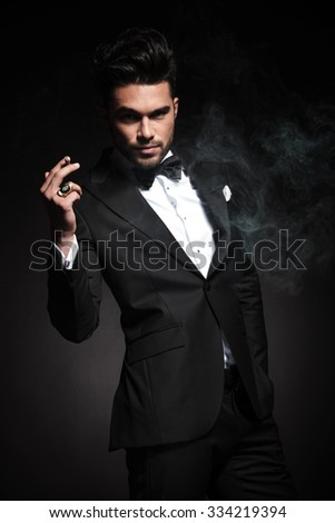 Handsome young business man enjoying a cigarette while holding one hand in his pocket.