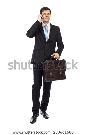 Handsome young business man holding a suitcase and talking on phone over white background