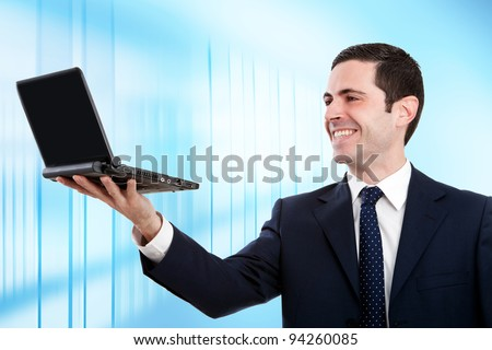Handsome young business man in blue suit raising laptop in office. - stock photo