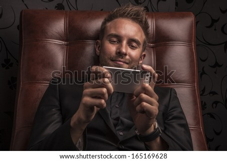 Handsome young business man in dark suit relaxing on luxury sofa.  - stock photo