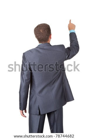 Handsome young business man in modern elegant suit standing back and pointing finger, isolated over white background. Concept of communication, information, social network, push digital button.