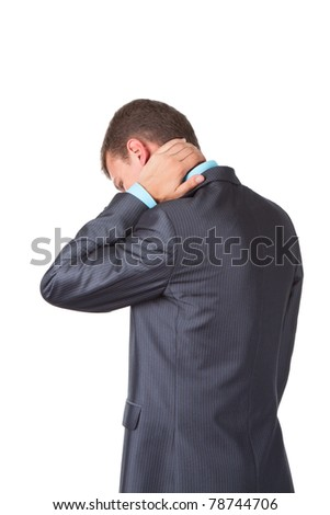 Handsome young business man in modern elegant suit standing back holding neck with his hands, isolated over white background. Concept of neck or head ache, pain, problem, tired up.