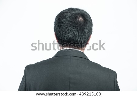 Handsome young business man in modern elegant suit standing back, isolated over white background. Concept of idea, ask question, think up, choose, decide, relax.