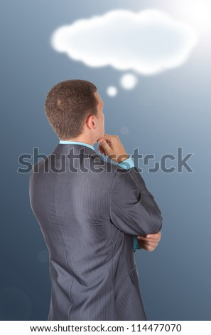 Handsome young business man in modern elegant suit standing back looking at drawing cloud with empty copy space, isolated over white background. Concept of idea, ask question, think up, choose, decide - stock photo