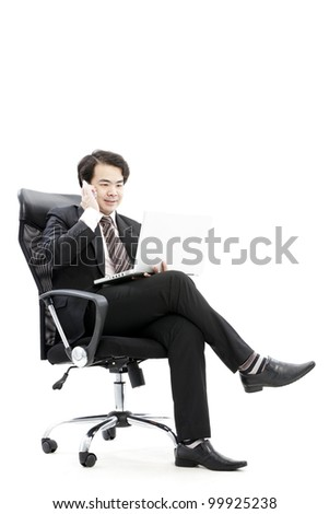 Handsome young business man on phone while using computer at workplace