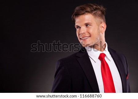 handsome young business man posing , looking over his shoulder and smiling, on a dark background - stock photo