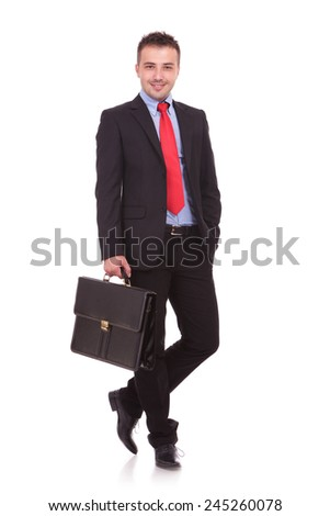Handsome young business man posing on white studio background, holding a black briefcase in his hand.