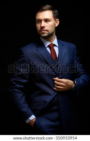 Handsome young business man standing on black  - stock photo