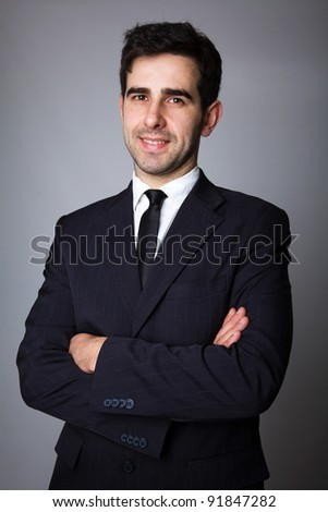 Handsome young business man standing on grey background - stock photo
