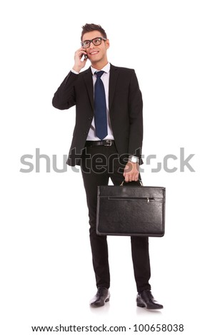 handsome young business man talking on a  mobile phone and holding a suitcase on white background - stock photo