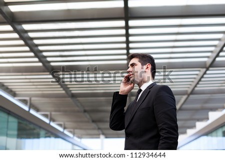 Handsome young business man talking on cell phone at modern office