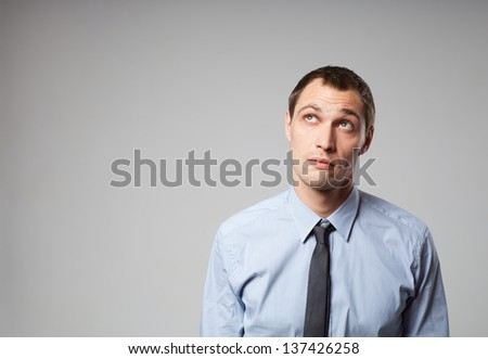 Handsome young business man thinking against gray background - stock photo