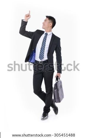 handsome young business man walking carrying a suitcase showing pointing,