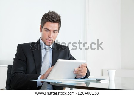 Handsome young businessman at desk with digital tablet and coffee cup in office - stock photo