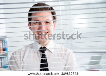Handsome young businessman at the office blinds.