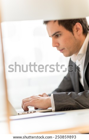 Handsome young businessman concentrating on his work as he sits at his desk navigating the internet on his laptop computer while reading the screen, profile view.