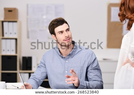 Handsome Young Businessman Discussing Something to his Female Office Mate at his Desk with Laptop Computer. - stock photo