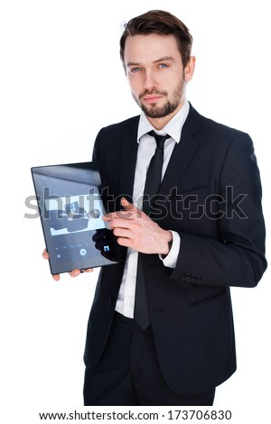 Handsome young businessman displaying a handheld tablet computer showing an image of himself to the viewer, isolated on white