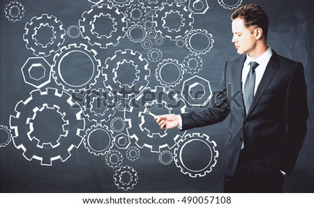 Handsome young businessman drawing cogwheels on chalkboard. Teamwork concept