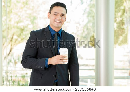 Handsome young businessman drinking a cup of coffee and smiling - stock photo
