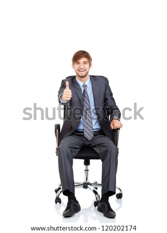 Handsome young businessman hold hand with thumb up gesture sitting in chair, business man excited happy smile, wear elegant shirt and tie isolated over white background