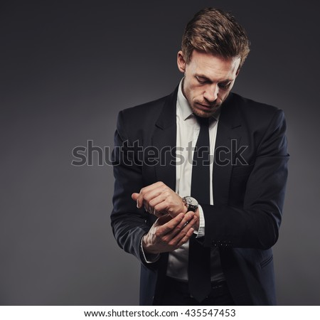 Handsome young businessman in a black suit checking the time on his watch, standing against a gray background