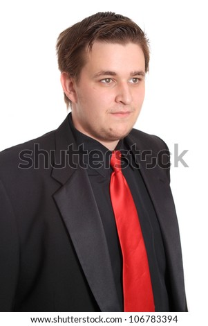 Handsome young businessman in black formal suit with red tie isolated on a white background