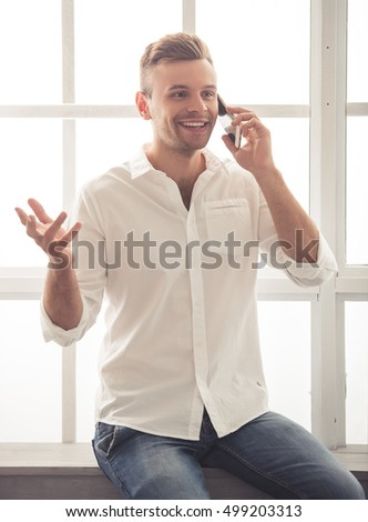 Handsome young businessman in classic shirt is talking on the mobile phone and smiling while sitting on the window-sill