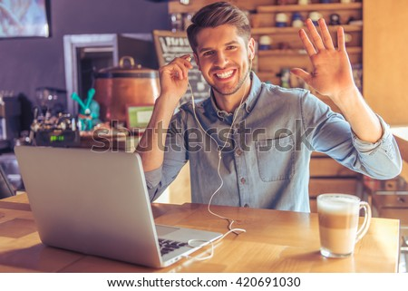 Handsome young businessman in headphones is using a laptop, waving and smiling while working in the cafe - stock photo
