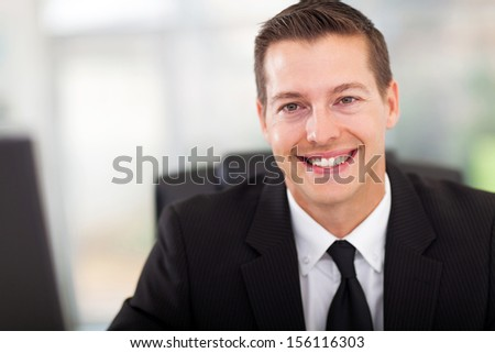 handsome young businessman in office looking at the camera