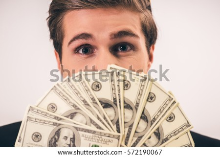 Handsome young businessman in suit is holding money and looking at camera, on gray background