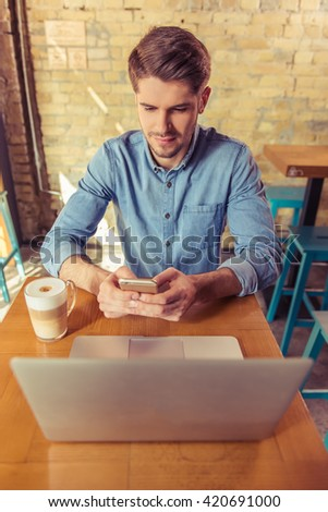 Handsome young businessman is using a laptop and a smartphone while working in the cafe - stock photo