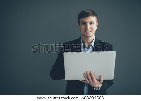 Handsome young businessman is using a laptop, looking at camera and smiling on black background