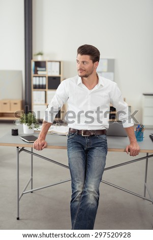 Handsome Young Businessman Leaning Leaning his Back Against the Office Table While Looking Into the Distance. - stock photo