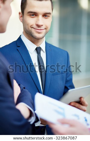 Handsome young businessman looking at camera at meeting