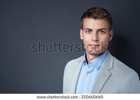 Handsome young businessman looking at the camera with a serious expression against a blackboard with copyspace, head and shoulders view - stock photo
