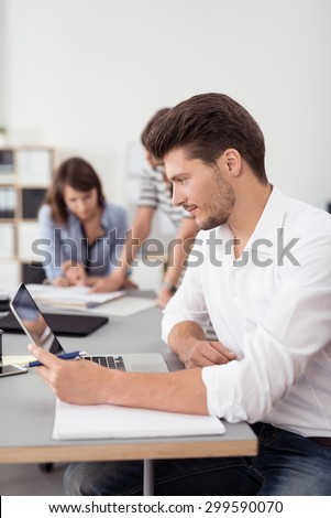 Handsome Young Businessman Looking Straight at his Laptop Screen on Top of the Table Inside the Boardroom.