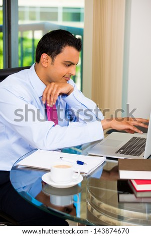 Handsome young businessman or student drinking coffee and working on laptop, isolated on a city background - stock photo