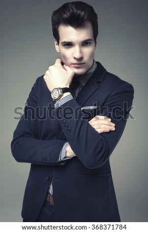 Handsome young businessman posing in studio, wearing elegant fashionable suit and watch. Man looking at camera. - stock photo
