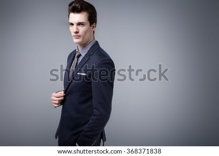 Handsome young businessman posing in studio, wearing elegant fashionable suit. Man looking at camera. - stock photo